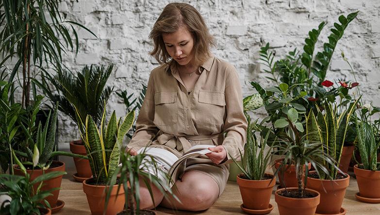 bitkiler arasında kitap okuyan kadın